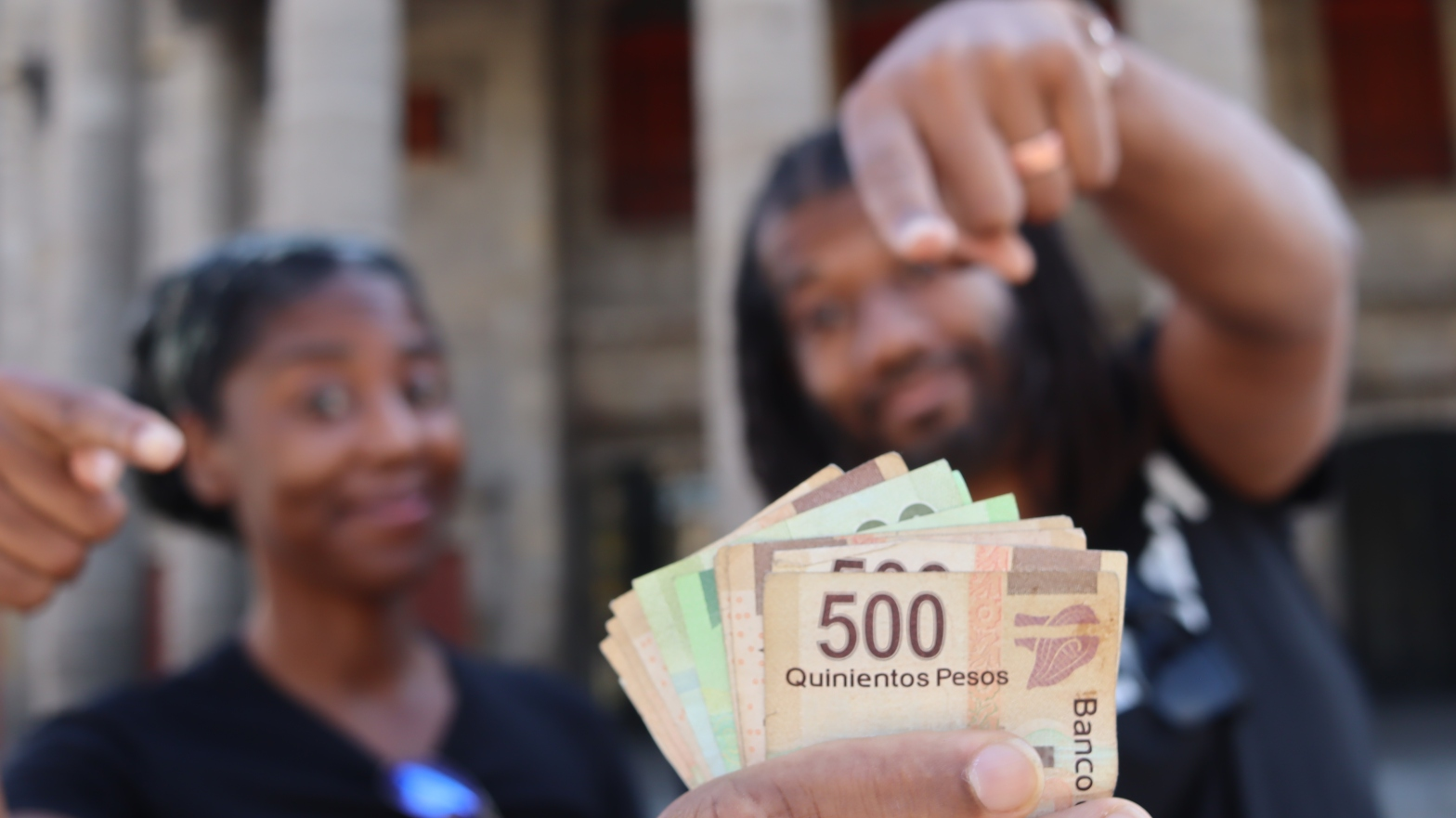 Shows couple pointing to pesos to highlight the cost of living in Guadalajara costs.